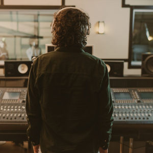 back view of sound producer in headphones at studio